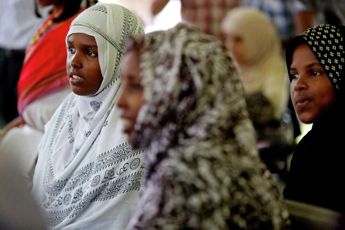Nimo Adan, 16, left, and sister Hawo Adan, 10, far right, of Somalia, now reside in Houston. They were among visitors Saturday to the University of St. Thomas to celebrate World Refugee Day with cultural entertainment and educational exhibits.