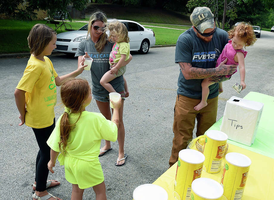 Jeremy Sandoval holds his daughter Maci, 2, as she drops her tip into the collection box, Saturday, June 13, 2015, in Overton, Texas.  8-year-old Andria Green and her 7-year-old sister, Zoey, whose lemonade stand was shut down because they lacked a permit will instead offer the drink for free Saturday in Overton, about 120 miles east of Dallas. (Andrew D. Brosig/The Tyler Morning Telegraph via AP) MANDATORY CREDIT Photo: Andrew D. Brosig, MBR / Tyler Morning Telegraph