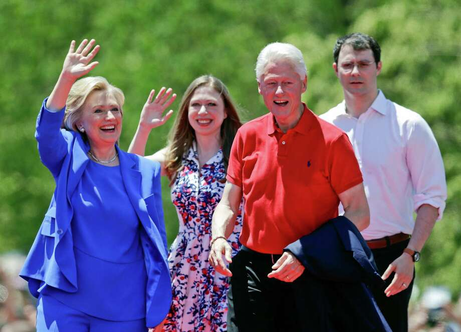 Democratic presidential candidate former Secretary of State Hillary Rodham Clinton waves to supporters as her husband former President Bill Clinton, second from right, Chelsea Clinton, second from left, and her husband Marc Mezvinsky, join on stage Saturday, June 13, 2015, on Roosevelt Island in New York.  (AP Photo/Frank Franklin II) Photo: Frank Franklin II, STF / AP