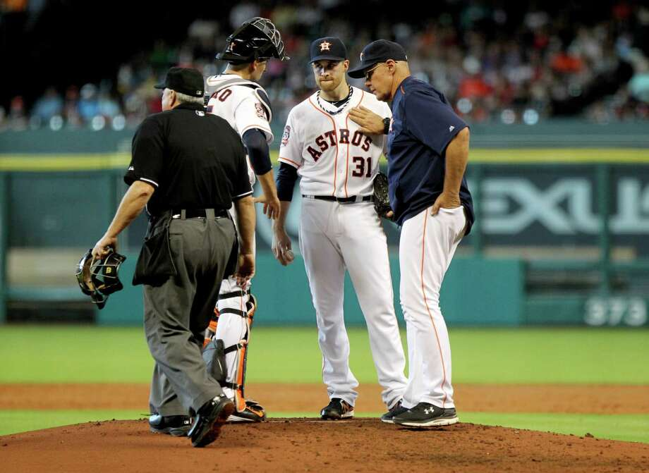 Astros starter Collin McHugh (31) gets advice during a three-run third that was his final inning of the day. Photo: Gary Coronado, Staff / © 2015 Houston Chronicle