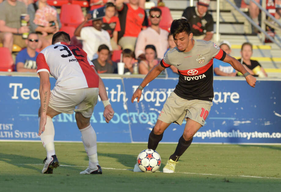 Scorpions Cesar Elizondo moves the ball past Ottawa's Colin Falvey during their North American Soccer League match Saturday at Toyota Field. Photo: Robin Jerstad, Freelance / San Antonio Express-News