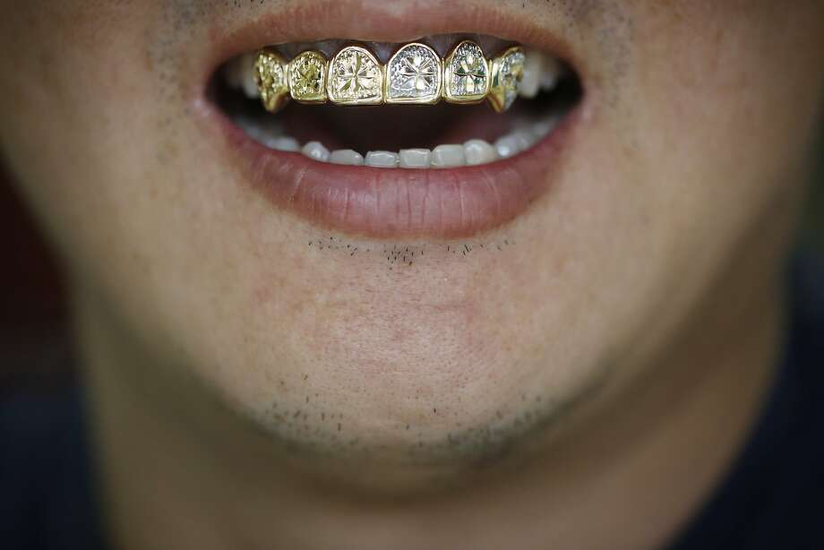 """David """"Mr. Bling Bling"""" Moon shows off his custom smile at his gold teeth shop of 15 years in San Francisco in 2008. He often uses his own teeth to help customers visualize their designs. Photo: Mike Kepka, The Chronicle"""