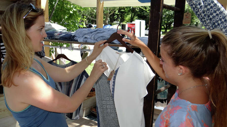 Pop Shop Market co-founder Andrea Espach consults on an outfit with Tai Truglio of Faherty Brand at the weekend-long Pop Shop Market on Town Hall Green. Photo: Mike Lauterborn / Mike Lauterborn / Fairfield Citizen