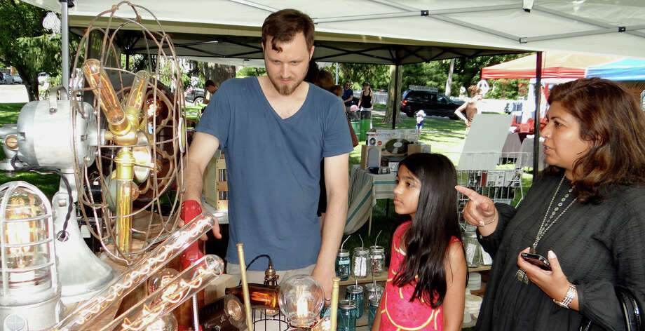 Jason Aleksa, owner of Stonehill Design, talks about his lighting creations with Preeti Butani and daughter Sanaa, 8, at the Pop Shop Market. Photo: Mike Lauterborn / Mike Lauterborn / Fairfield Citizen