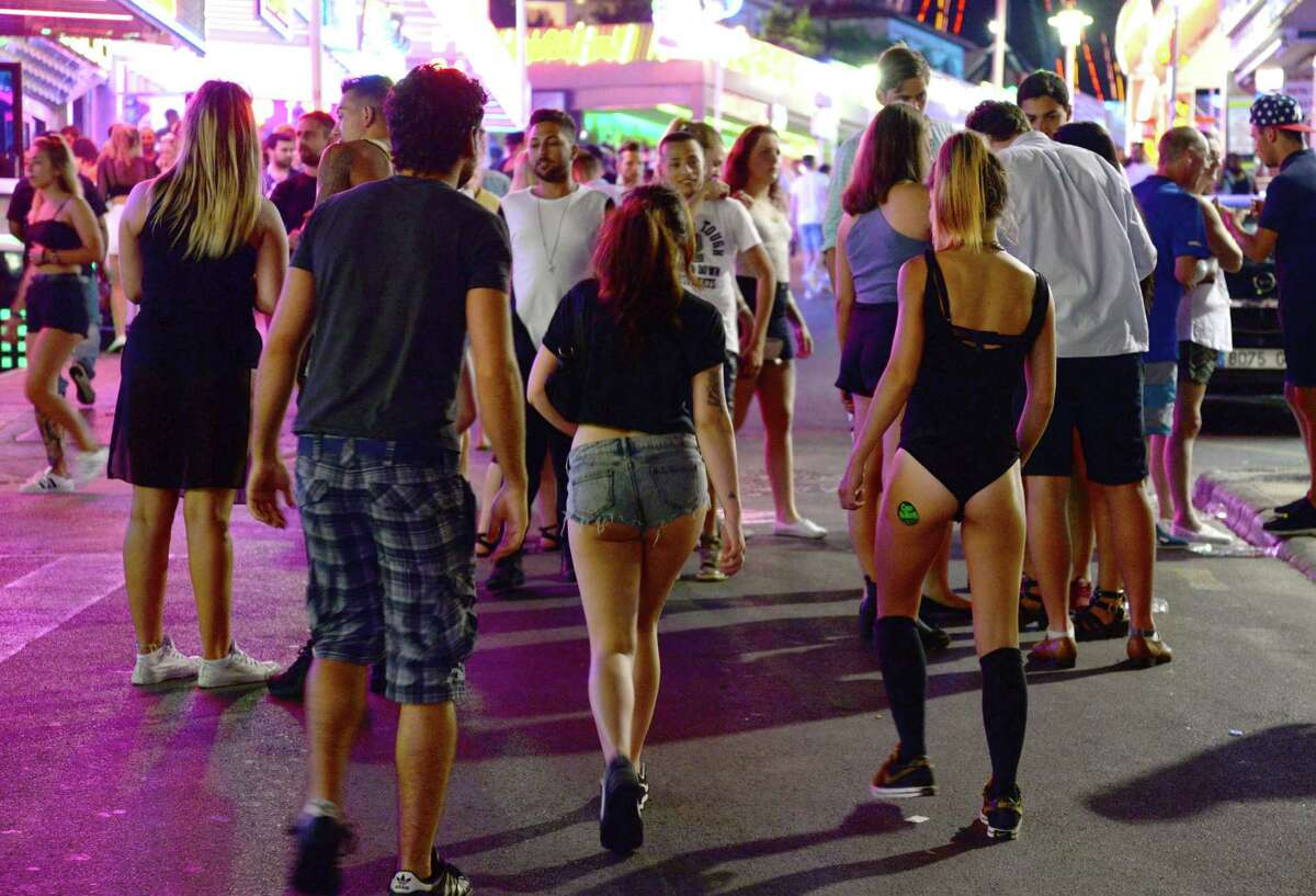 Tourists walk on the street at the resort of Magaluf, in Calvia town, on the Spanish Balearic island of Mallorca, Wednesday, June 10, 2015. Magaluf, the super popular Spanish resort notorious for the alcohol binges and drunken misbehavior of foreign tourists -- mostly young Britons -- is hoping a package of new municipal regulations will help clean up its image.