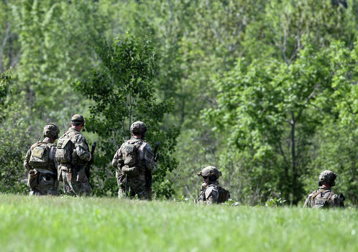 Law enforcement officers walk into the woods on Sunday, June 14, 2015, in Saranac, N.Y. Law enforcement personnel are in the ninth day of searching for David Sweat and Richard Matt, two killers who used power tools to cut their way out the prison in Dannemora in northern New York. (AP Photo/Mike Groll) ORG XMIT: NYMG103