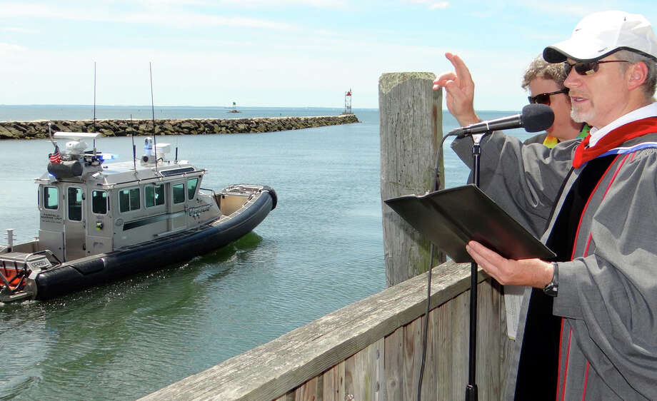 The Rev. Paul Whitmore of Southport Congregational Church blesses Fairfield fireboats as they pass Southport's Lower Wharf during the Blessing of the Fleet ceremony Saturday morning. Photo: Mike Lauterborn / Mike Lauterborn / Fairfield Citizen