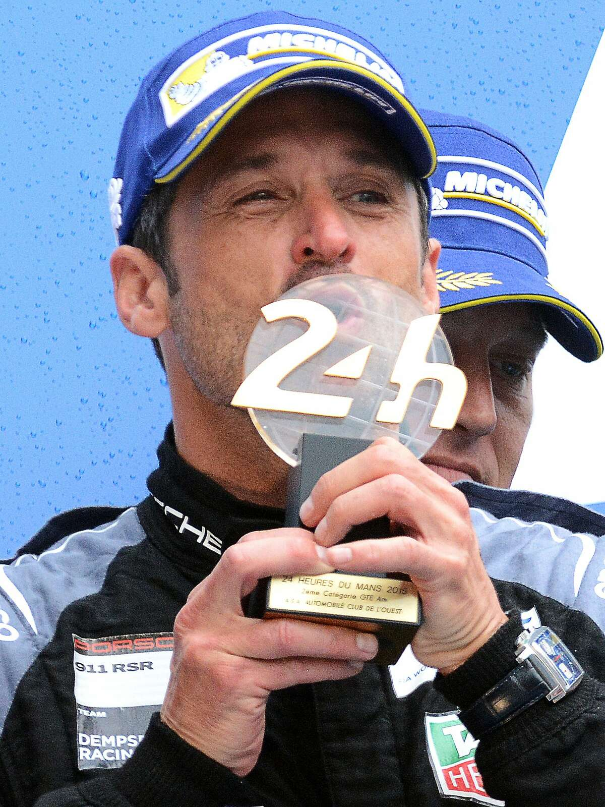 US Patrick Dempsey kisses his trophy on the podium the 83rd Le Mans 24 Hours endurance race on June 14, 2015 in Le Mans, western France, after taking secong place in the LMGTE-Am category with his Porsche 911 RSR N°77. US Patrick Long, Germany's Marco Seefried and US Patrick Dempsey took the second place LMGTE-Am category. AFP PHOTO / JEAN-FRANCOIS MONIERJEAN-FRANCOIS MONIER/AFP/Getty Images