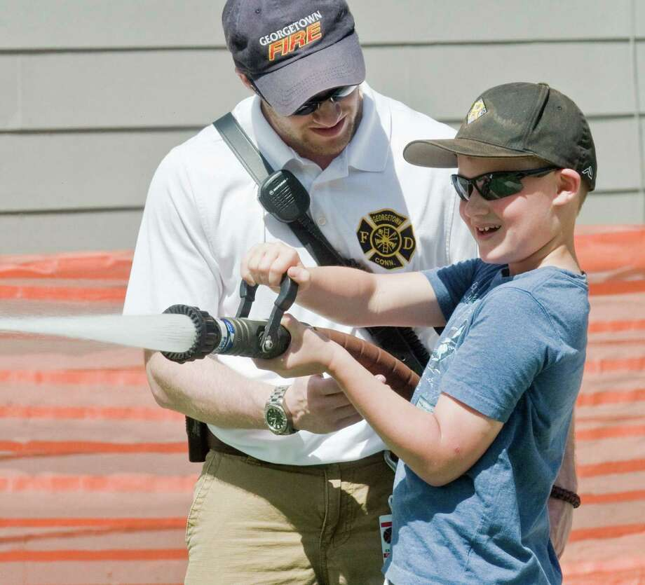 Goergetown Fire Department Lt. Liam Bauer helps eight-year-old James Pereira aim a fire hose at the 13th annual Georgetown Day on Main Street in Georgetown. Sunday, June 14, 2015 Photo: Scott Mullin / For The / The News-Times Freelance