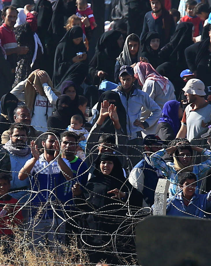 In this photo taken from the Turkish side of the border between Turkey and Syria, in Akcakale, Sanliurfa province, southeastern Turkey, Syrian refugees cheer and chant pro-Turkey slogans as they wait on the Syrian side of the border in order to cross, Sunday, June 14, 2015. The mass displacement of Syrians came as Kurdish fighters announced they are making headway toward the border town of Tal Abyad, a stronghold of the extremist group near the Turkish border. The loss of Tal Abyad would be a major blow to the Islamic State group as it is a major avenue for commerce for the extremist group.(AP Photo/Lefteris Pitarakis) Photo: Lefteris Pitarakis, STF / AP