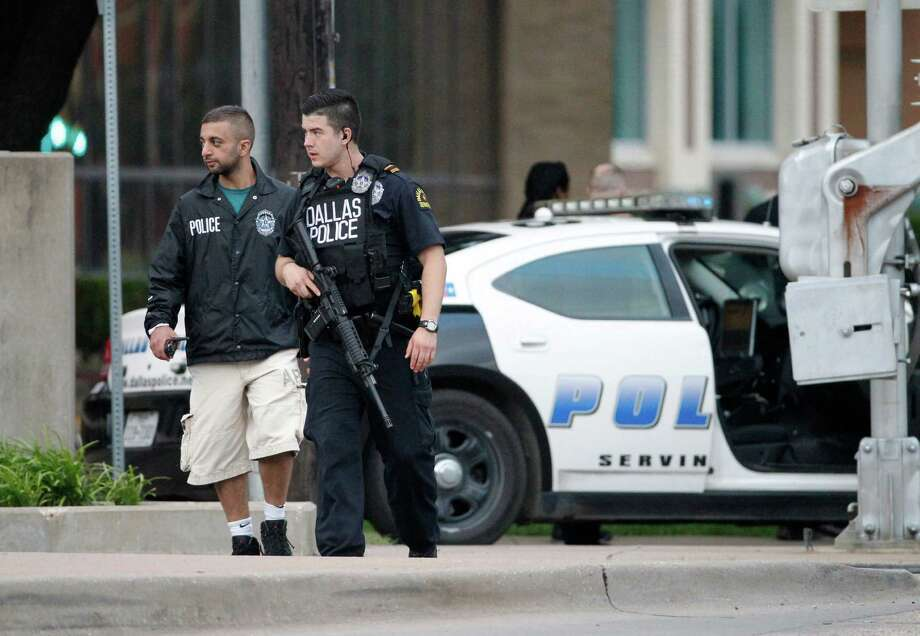Dallas police officers walk down Belleview Street one block away from police headquarters searching the area Saturday June 13, 2015, in Dallas. A police sniper shot a man suspected of an overnight attack on police headquarters and the department was checking to see if he's still alive, Police Chief David Brown said Saturday.  (AP Photo/Tony Gutierrez) Photo: Tony Gutierrez, STF / Associated Press / AP