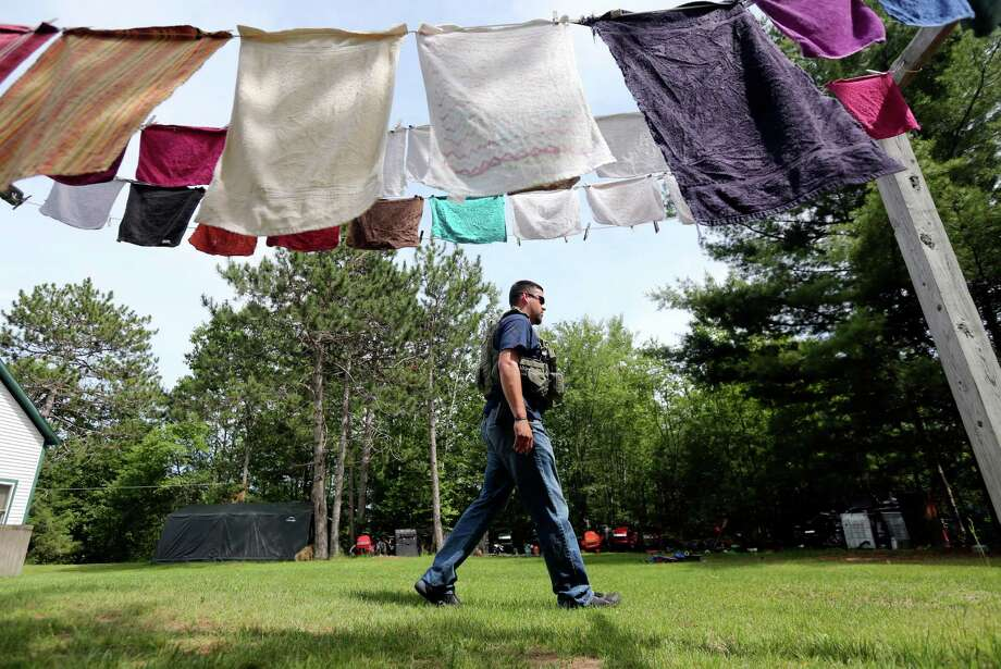 A law enforcement officer conducts a house-to-house search for escaped prisoners David Sweat and Richard Matt on Sunday in Cadyville, N.Y. It was the ninth day of searching for the pair. Photo: Mike Groll, STF / AP