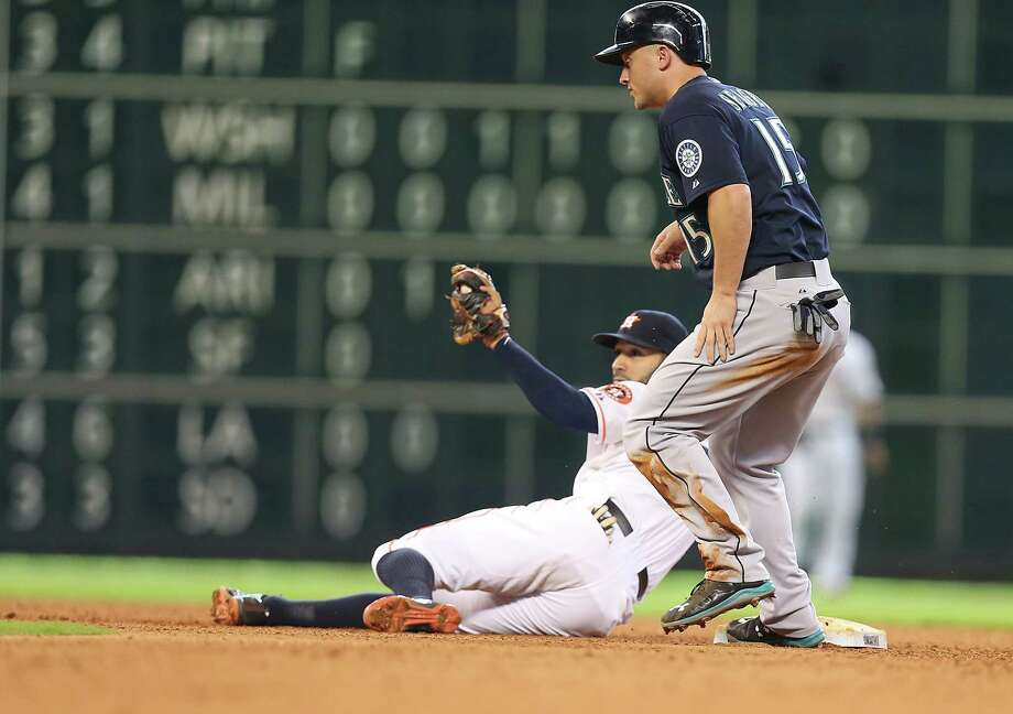 Astros shortstop Marwin Gonzalez hangs on to complete a force out of Kyle Seager, who had singled for the second of the Mariners' two hits Sunday. Photo: Mayra Beltran, Staff / © 2015 Houston Chronicle