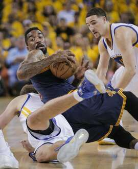 Cleveland Cavaliers' J.R. Smith rolls over Golden State Warriors' David Lee in the second period during Game 5 of The NBA Finals between the Golden State Warriors and Cleveland Cavaliers at Oracle Arena on Sunday, June 14, 2015 in Oakland, Calif.