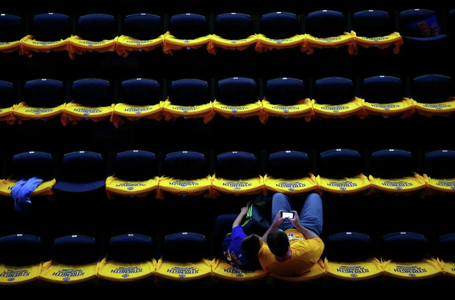 Golden State Warriors' fan Gallagher Jeff of Palo Alto and his son, Lucas, 9, wait the start of Game 5 of NBA Finals at Oracle Arena in Oakland, Calif., on Sunday, June 14, 2015. Photo: Scott Strazzante / The Chronicle / ONLINE_YES