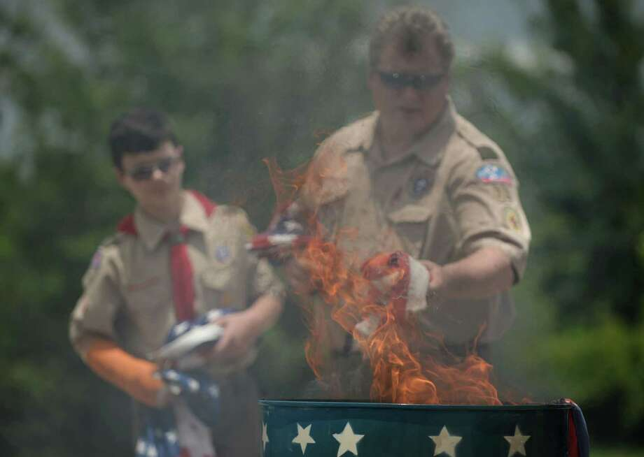 Zachary and Lloyd Funk, with Boy Scout Troop 73, burn old flags Sunday during a flag-retiring ceremony at the Katy Elks Lodge. Every year since 1937, the American Legion celebrates the holiday to commemorate the history  of the American flag.  Photo: Jon Shapley, Staff / © 2015 Houston Chronicle