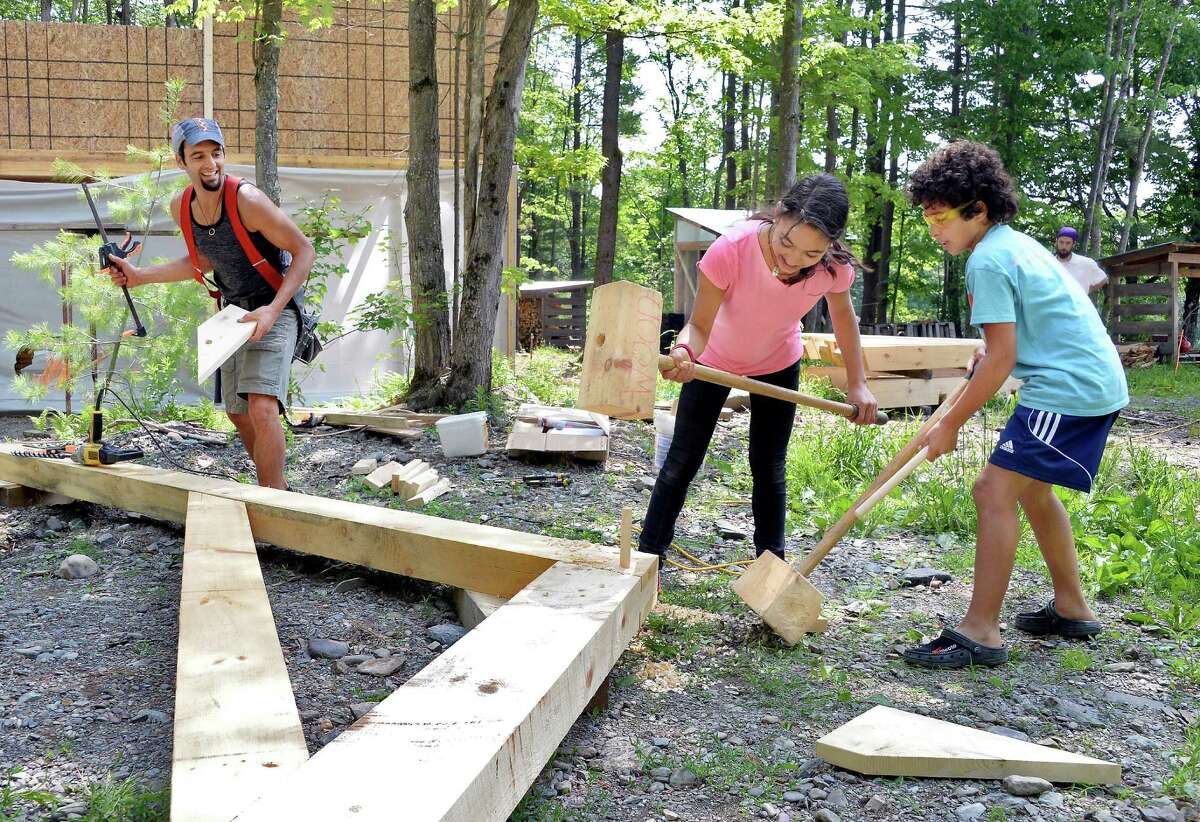 Jonah Vitale-Wolff, left, gets help from his children Neshima Vitale-Penniman, 12, and Emmet Vitale-Penniman, 10, prepping a timbered roof truss for their upcoming barn raising at their Soul Fire Farm Thursday June 11, 2015 in Grafton, NY. (John Carl D'Annibale / Times Union)