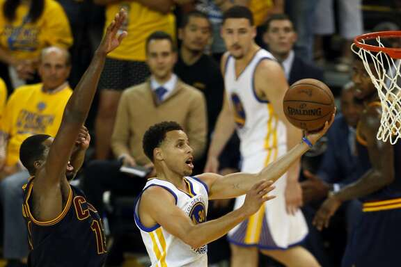 Golden State Warriors' Stephen Curry scores against Cleveland Cavaliers' Tristan Thompson in 4th quarter of Warriors' 104-91 win during Game 5 of NBA Finals at Oracle Arena in Oakland, Calif., on Sunday, June 14, 2015.