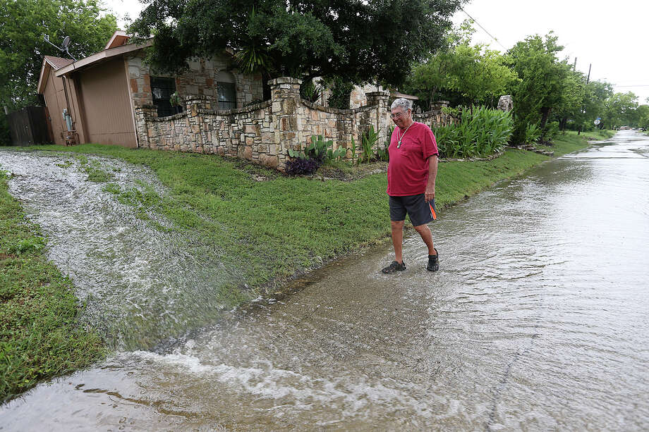 "Jesse Arguello, 74, walks through the water in the 500 block of Emory Street in the Woodlawn Lake area after thunderstorms rolled through San Antonio. ""Feels very relaxing,"" he said. Photo: Jerry Lara /San Antonio Express-News / © 2015 San Antonio Express-News"