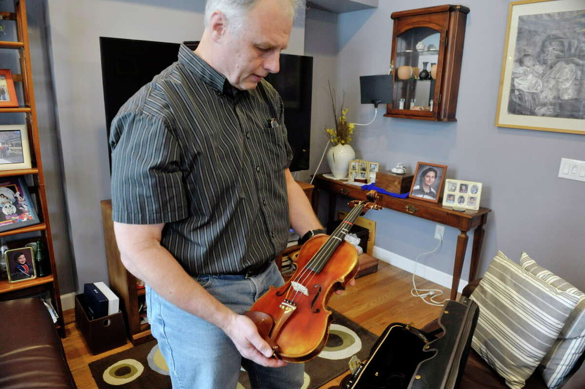 Doug Van Zandt holds the violin that his son played as he talks about his son Benjamin during an interview on Thursday, March 5, 2015, in Albany, N.Y. Benjamin Van Zandt hung himself in his prison cell a few months ago at age 21. (Paul Buckowski / Times Union)