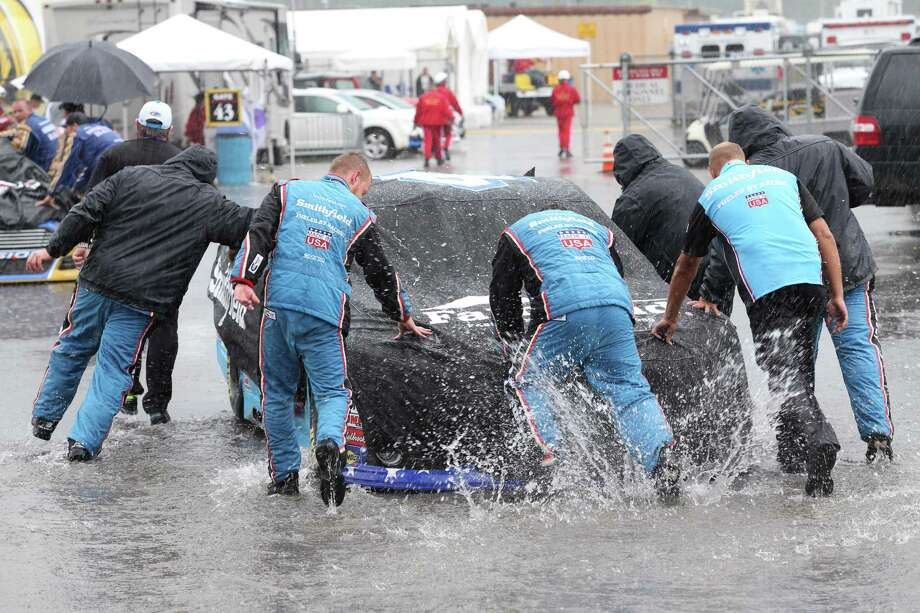 The crew for Aric Almirola works during a pit stop that didn't end because of the weather, forcing the Sprint Cup race to be shortened by 62 laps. Photo: Dave Frechette, FRE / AP