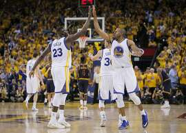 Golden State Warriors' Draymond Green and Andre Iguodala high five in the fourth period during Game 5 of The NBA Finals between the Golden State Warriors and Cleveland Cavaliers at Oracle Arena on Sunday, June 14, 2015 in Oakland, Calif.
