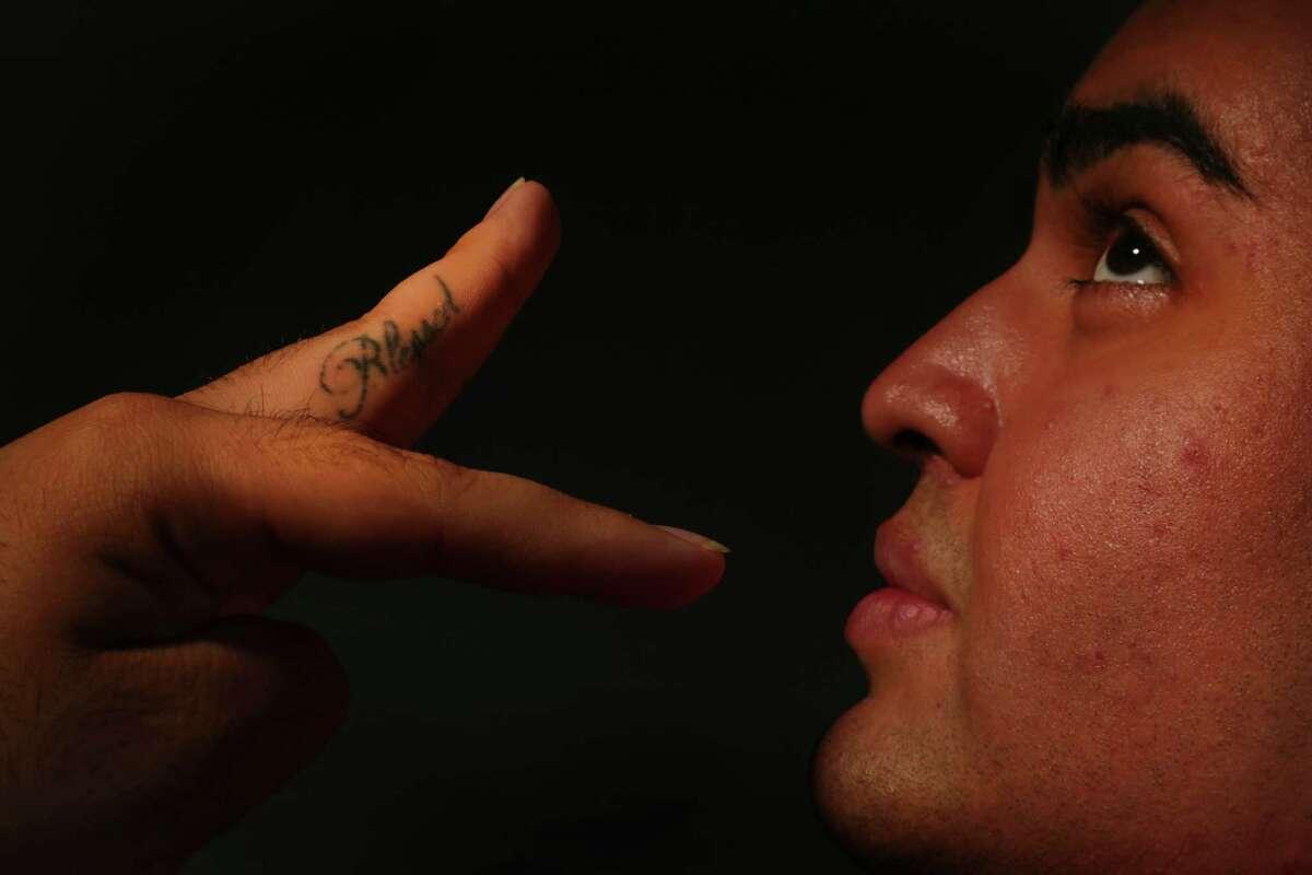 Juan de la Garza shows the matching tattoo of the word