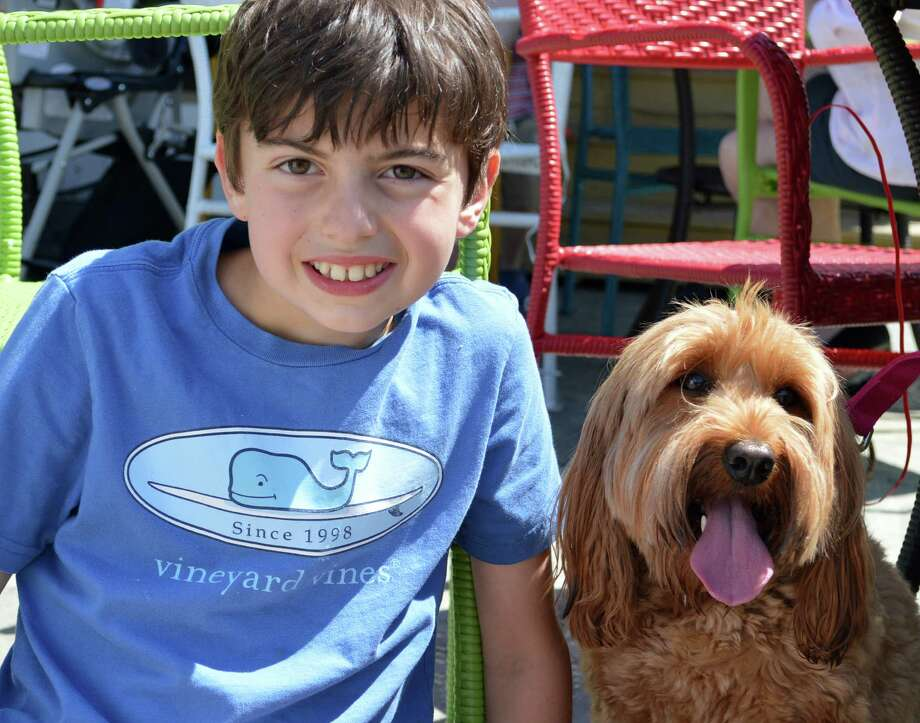 Ben Saxon, 10, of Westport, and his dog Ozzy visited Saugatuck Sweets on Saturday to support the Westport Animal Shelter Advocates fundraiser. Photo: Jarret Liotta / Jarret Liotta / Westport News