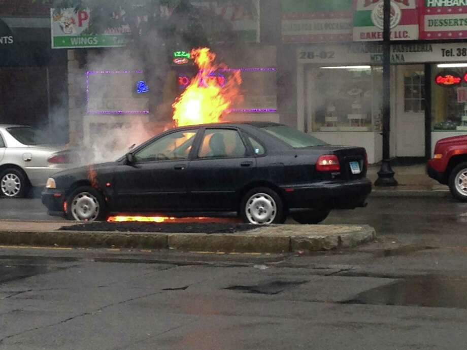 A car fire Monday morning on Fairfield Avenue between Brewster and Haddon Streets in the Black Rock section of Bridgeport briefly snarled traffic while firefighters put out the flames. Photo: Erin Walsh / Hearst Connecticut Media