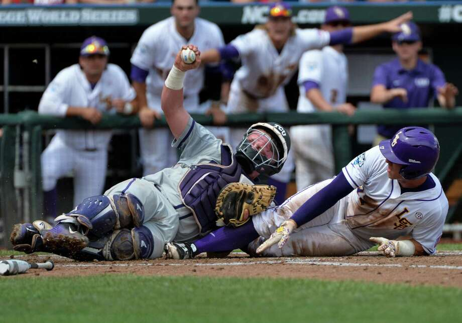 TCU catcher Evan Skoug, left, holds up the ball after tagging out LSU second baseman Jared Foster in the third inning of an NCAA College World Series baseball game at TD Ameritrade Park in Omaha, Neb., Sunday, June 14, 2015. (AP Photo/Ted Kirk) Photo: Ted Kirk, FRE / Associated Press / FR34398 AP