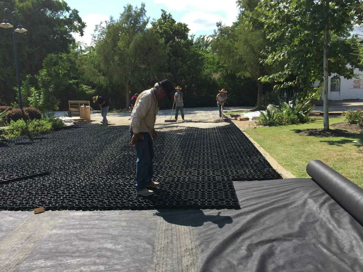 At Ninfa's: Workers install the tough plastic grid that will give the parking lot its structure.