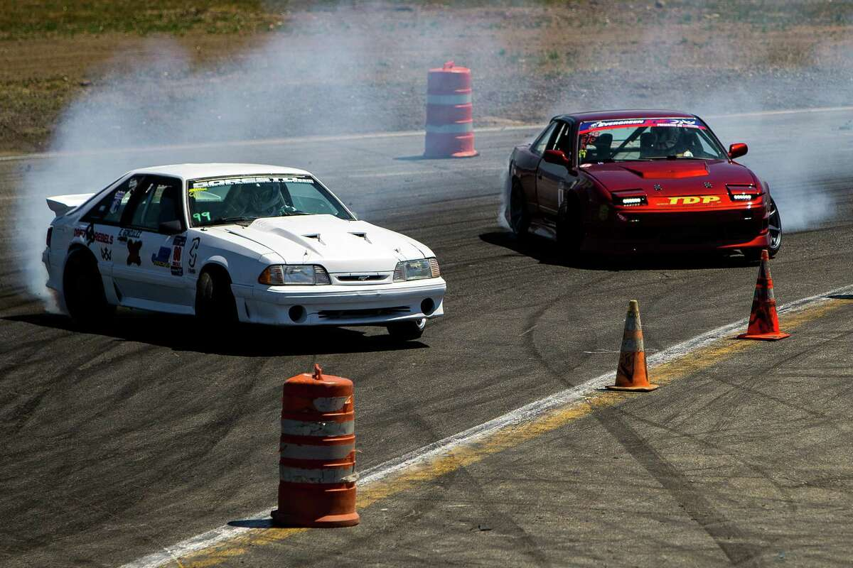 Vehicles slide sideways, rounding corners and traffic cones at DriftCon, an import car show and drift event, photographed Sunday, June 14, 2015, at Evergreen Speedway in Monroe, Washington. Drifting is a worldwide motorsport discipline, judged on speed, angle, showmanship and path that a car takes while navigating through a set of corners.