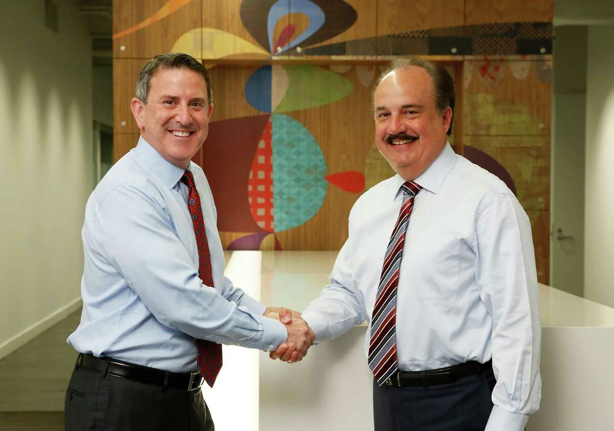 IMAGE DISTRIBUTED FOR TARGET AND CVS HEALTH - Target Chairman and CEO Brian Cornell, left, and CVS Health President and CEO Larry Merlo, right, meet up in New York, Monday, June 15, 2015, to announce a strategic agreement. Under the agreement, CVS Health will acquire, rebrand and operate Target's pharmacies and clinics. (Stuart Ramson/AP Images for Target and CVS Health)