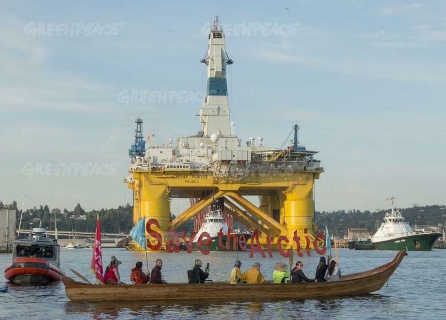 "Activists in a tribal canoe hoist a ""Save The Arctic"" message as they stand in the way of Shell's Polar Pioneer drilling rig as attempts to depart Elliott Bay for Alaska.  The Polar Pioneer is one of two drilling vessels heading towards the Arctic for Shell this year. The second, the Noble Discoverer, is one of the oldest drill ships in the world. Photo: © Marcus Donner / Greenpeace"