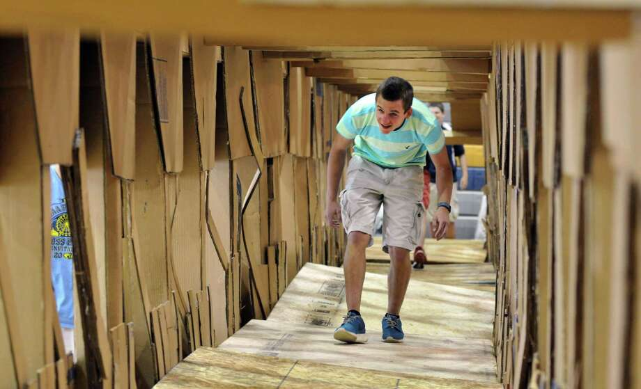 10th grader, Zak Gregware, walks through the cardboard bridge Monday, June 15, 2015, at Averill Park High School in Averill Park, N.Y. The bridge was 72-feet-long and took four weeks to build. Students in the school?s principles of engineering classes, taught by Matthew Duff, learned about statics and strength of materials with the goal of applying what they learn to the end-of-the-year project ? a life size bridge they build with only cardboard and Elmer's school glue. (Phoebe Sheehan/Special to the Times Union) Photo: PS / 00032262A