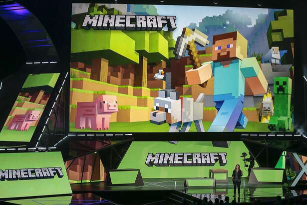 """Lydia Winters, at podium, shows off Microsoft's """"Minecraft"""" built specifically for HoloLens during a live demo at the Xbox E3 2015 briefing ahead of the Electronic Entertainment Expo at the University of Southern California's Galen Center on Monday, June 15, 2015 in Los Angeles. Microsoft is promoting the next installment in its popular sci-fi franchise, """"Halo 5: Guardians,"""" at the Electronic Entertainment Expo. (AP Photo/Damian Dovarganes)"""