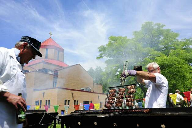 Bob Bedian, left, and Ron Kaiser work over a hot grill as they cook lamb at the Armenian Festival at St. Peter Armenian Church on Sunday, June 8, 2014, in Watervliet, N.Y.  Over 900 pounds of lamb were served at the two-day event.   The annual event features  Armenian foods, music and games.   (Paul Buckowski / Times Union) ORG XMIT: MER2014060816461487 Photo: Paul Buckowski / 00027261A