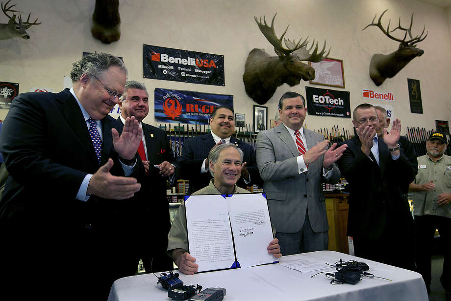 Gov. Greg Abbott signs into law bills to allow concealed carrying of handguns on college campuses and open carrying of them elsewhere in the state Saturday at Red's Indoor Range in Pflugerville.  (Ralph Barrera / Austin American-Statesman via Associated Press) Photo: Ralph Barrera, MBO / Austin American-Statesman