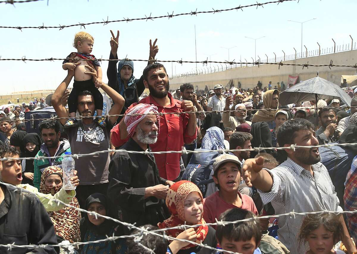 Syrian refugees mass at the Turkish border while they flee intense fighting in northern Syria between Kurdish fighters and Islamic State militants in Akcakale, southeastern Turkey, Monday, June 15, 2015. The flow of refugees came as Syrian Kurdish fighters closed in on the outskirts of a strategic Islamic State-held town on the Turkish border.(AP Photo/Lefteris Pitarakis)