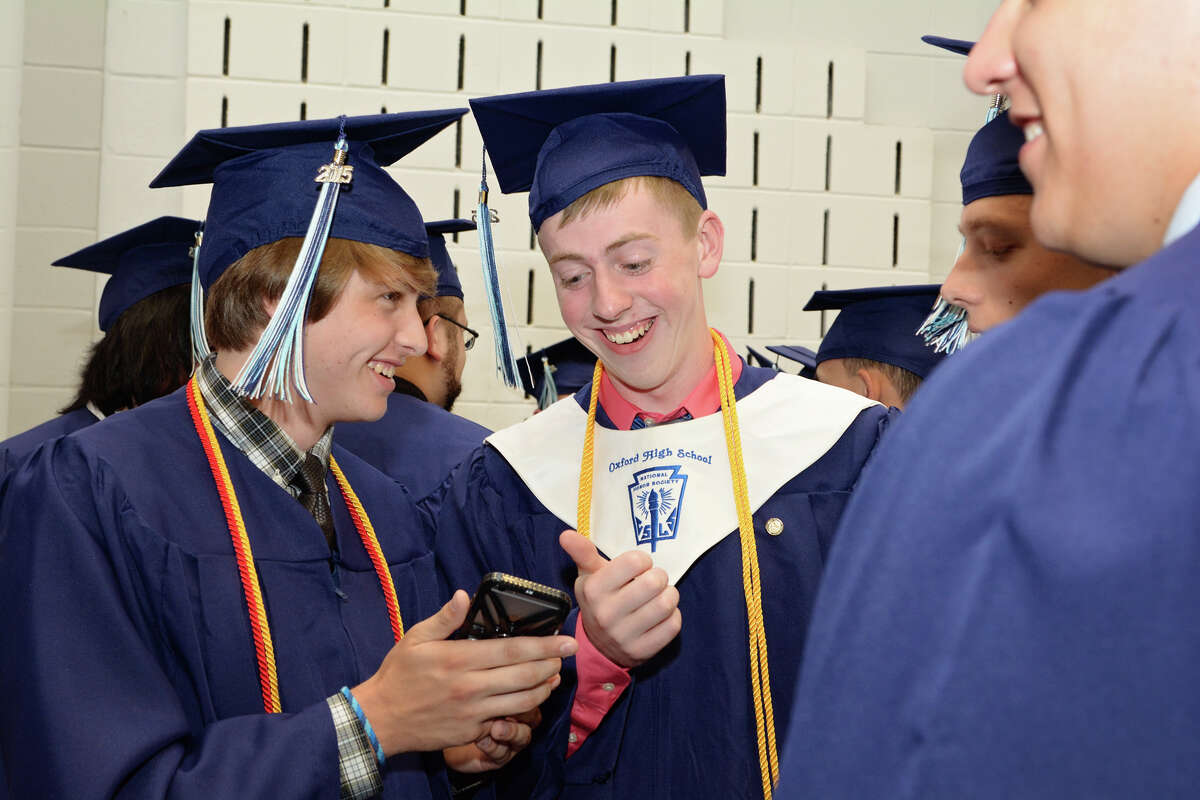 Graduate Richard Smith, at right, gives classmate, Zachary Geffert, a thumbs up prior to the start of Oxford High School's commencement exercises on Monday, June 15, 2015.