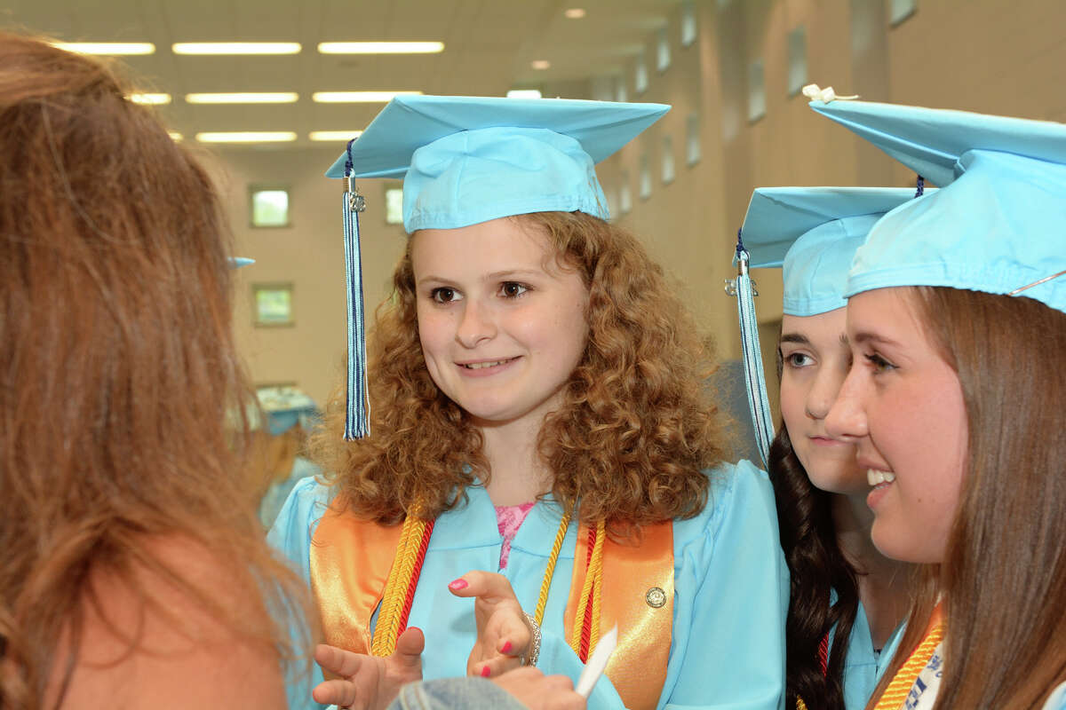 Valedictorian, Margaret Palys, enjoys a moment with friends and classmates prior to the start of Oxford High School's commencement exercises on Monday, June 15, 2015.