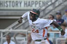 Miami's Jacob Heyward (24) celebrates a go-ahead run after a series of throwing errors by Arkansas, in the seventh inning of an NCAA College World Series baseball elimination game at TD Ameritrade Park in Omaha, Neb., Monday, June 15, 2015. (AP Photo/Mike Theiler)