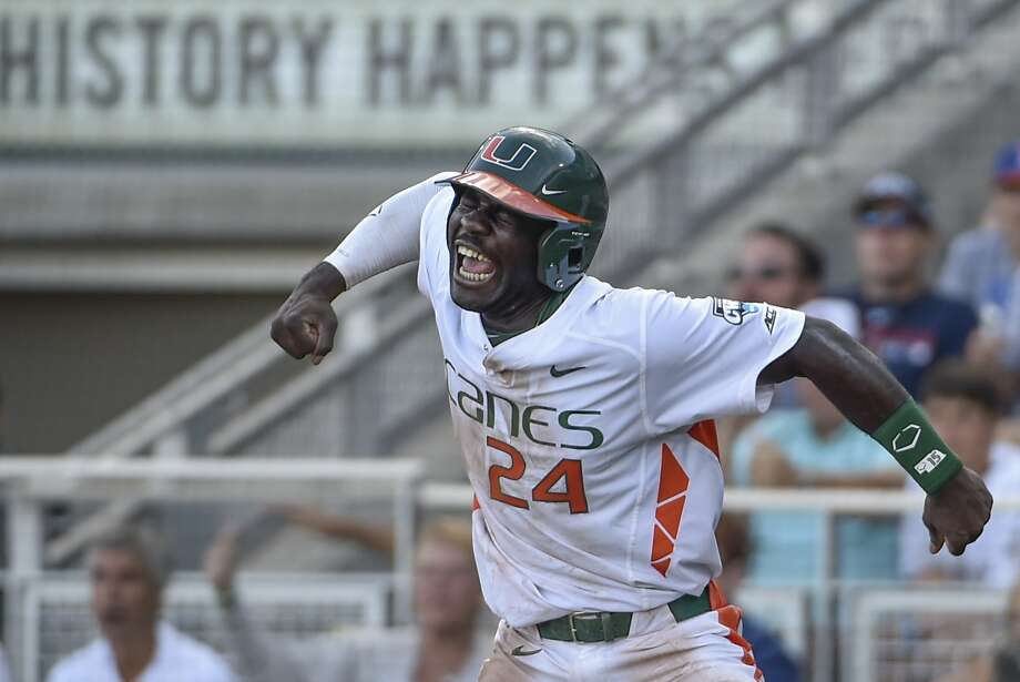 Miami's Jacob Heyward (24) celebrates a go-ahead run after a series of throwing errors by Arkansas, in the seventh inning of an NCAA College World Series baseball elimination game at TD Ameritrade Park in Omaha, Neb., Monday, June 15, 2015. (AP Photo/Mike Theiler) Photo: Mike Theiler, Associated Press
