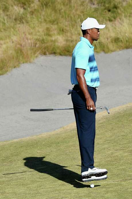 Tiger Woods has to move his foot to avoid being hit by a ball rolling down one of Chambers Bay's many sloped surfaces. Photo: Ross Kinnaird, Staff / 2015 Getty Images