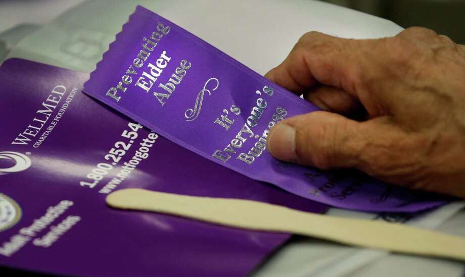Pedro Vera, 93 years old, holds ribbon given out at a rally to end elder abuse, at the Elvira Cisneros Senior Community Center on Monday June 15, 2015. Photo: Bob Owen, Staff / San Antonio Express-News / San Antonio Express-News