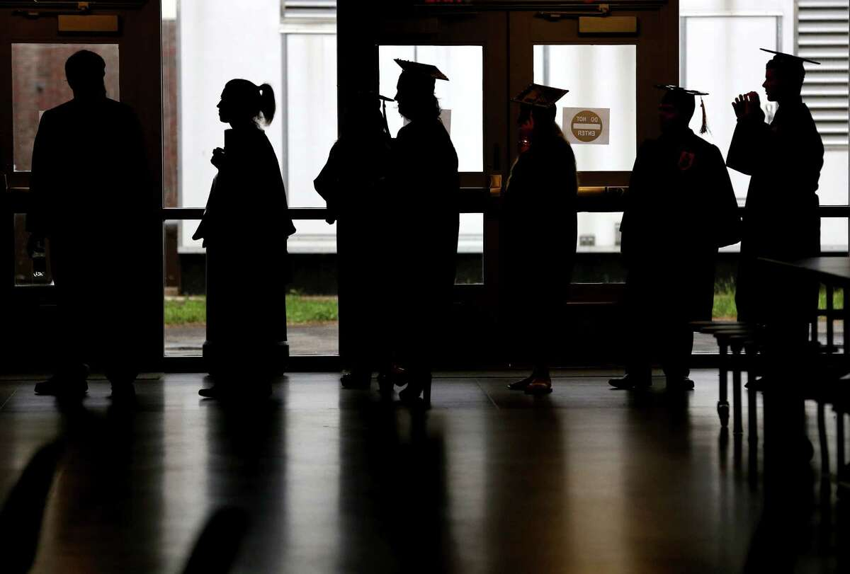 Trumbull High School students are silhouetted as they make their way for commencement exercises in gym on Monday.