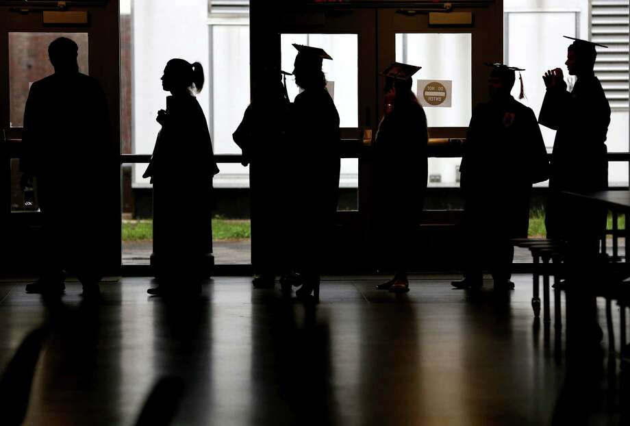 Trumbull High School students are silhouetted as they make their way for commencement exercises in gym on Monday. Photo: Mike Ross, For The / Connecticut Post Freelance