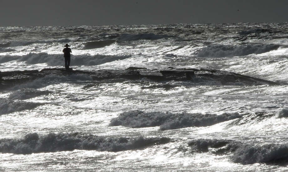 """I'm concerned,"" Rich Banks says as he takes photos of the rising waves from a Galveston jetty on Monday.   Photo: Cody Duty, Staff / © 2015 Houston Chronicle"