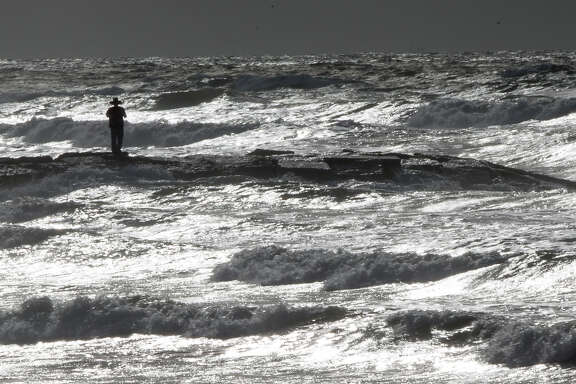 """""""I'm concerned,"""" Rich Banks says as he takes photos of the rising waves from a Galveston jetty on Monday."""
