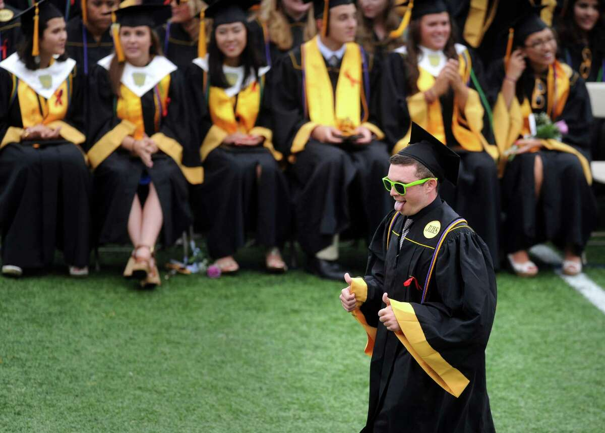 Graduate Mac Taylor walks across the field to accept his diploma Monday, June 15, 2015, during the Jonathan Law High School commencement at the school in Milford, Conn.